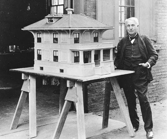 Thomas Edison next to his model of the single pour concrete home.
